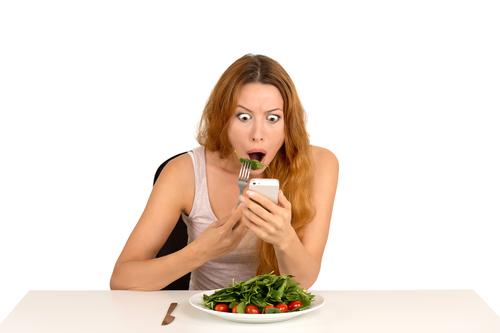 Shocked girl eating green salad looking at phone seeing bad breaking news